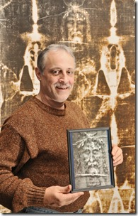 """Dave Onesko of Middleburg Heights stands alongside these 8 feet """"Shroud of Turin"""" murals at the Grace Fellowship Church where he will be giving a presentation. (Kyle Lanzer/Sun News)"""